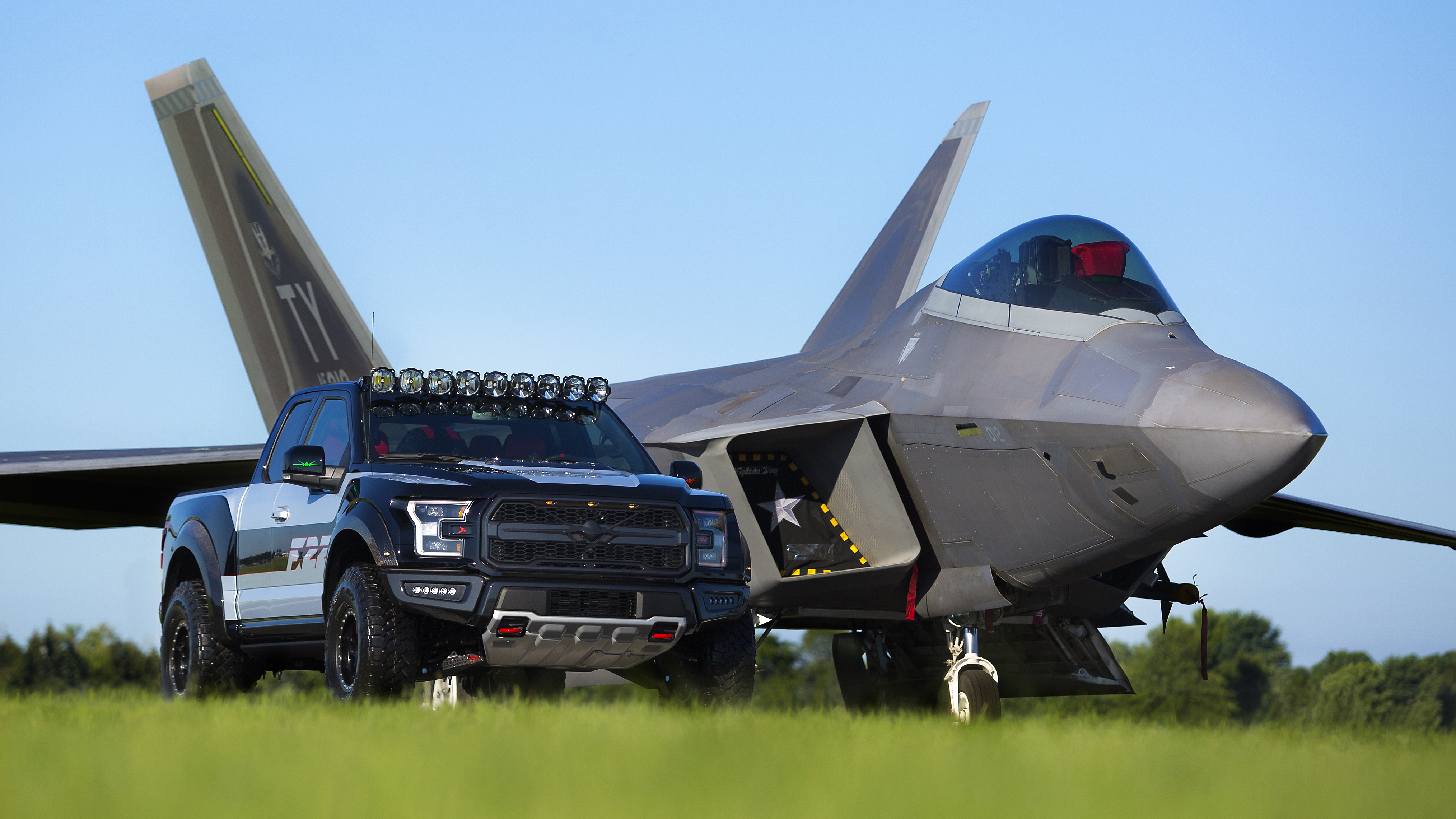 Ford F-150 Raptor next to F-150 fighter jet